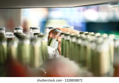 Close up of drink shelf in supermarket. Alcohol, soda, sodapop, mineral water or ginger ale bottle. Customer buying product in grocery store or liquor shop. Retail worker filling and stocking shelves.