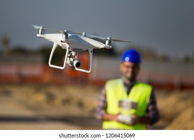 Close up of drone flying at building site and construction worker with remote control in background