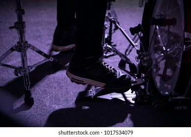 close up of drummer's foot wears sneakers moving drum bass pedal during recording  the music on drum set in  the studio.Rock musician playing the music