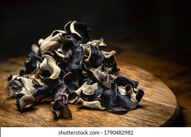 Close up of dry black sliced mushroom on wooden background. Edible dark fungus - auricularia polytricha. Nobody