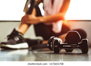 Close up dumbbells with woman exercise workout in gym fitness breaking relax after sport training with protein shake bottle background. Healthy lifestyle bodybuilding and athlete muscles lifestyle.