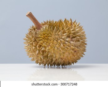 Close up of a durian on marble surface over gray background.