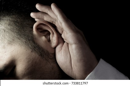 Close up ear of a middle aged businessman wearing hearing aid and listening for a sound.