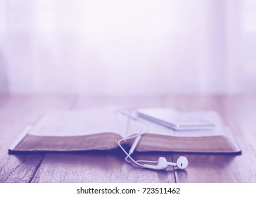 close  of  earphone over opened holy bible  with smart  phone  on wooden table with the light from above with copy space fro your text. christian background.