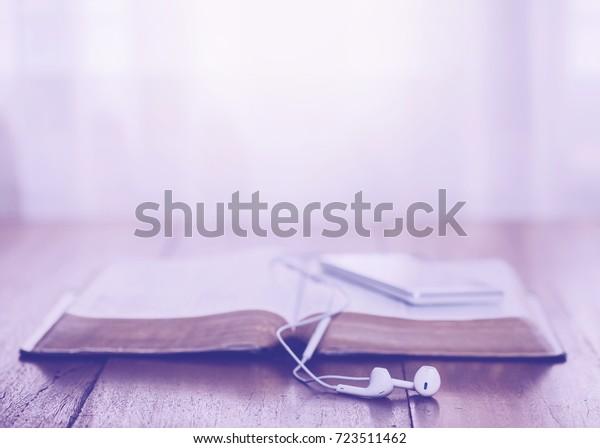 Nahaufnahme des Kopfhörers über geöffnete heilige Bibel mit Smartphone auf Holztisch mit dem Licht von oben mit Kopienraum für Ihren Text. christlicher Hintergrund.
