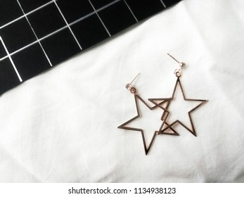 Close up of earring minimal style jewelry stars daimond silvers is earring,on whit fabric minimal style.