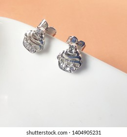 Close up of earring minimal style jewelry daimond silvers is Cupcakes earring,on white wooden minimal style.