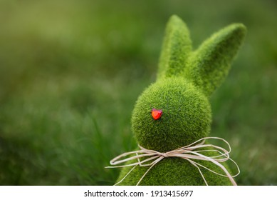 Close up Easter bunny rabbit statuette and basket with easter eggs on the green grass lawn background. Easter egg hunt in the garden. Selective focus, copy space