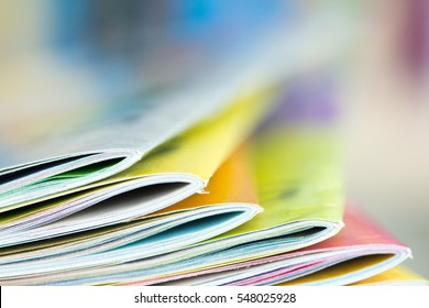 Close up edge of colorful magazine stacking with  blurry bookshelf background for publication and publishing concept , extremely DOF