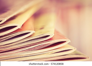 Close up edge of colorful magazine stacking with  blurry bookshelf background for publication and publishing concept , extremely DOF with vintage retro color tone