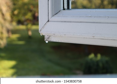 Close up of edge of open window frame showing water droplets forming on lower edge with blurred bokeh background