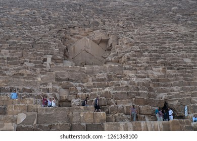 Close up of egypt pyramids with perople there climbing up at the great stones