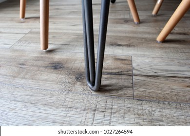 Close up of Eiffel chair legs and hair pin table leg in focus, with laminate floor background