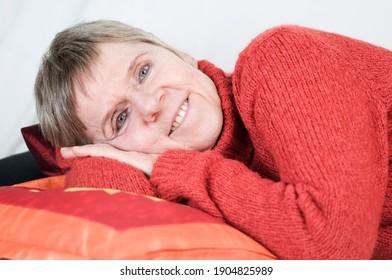 Close up einer älteren Frau auf der Seite liegend und in die Kamera lächelnd vor weißen Hintergrund. - Shutterstock ID 1904825989