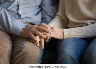 Close up elder family couple sitting on sofa, holding hands, old loving married man supporting wife, mutual understanding, psychological help, comforting, taking care of each other.