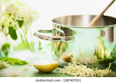 Close up of elderflowers, lemon and sugar on kitchen table with cooking pot. Homemade elderflower syrup or jam making. Healthy elder flowers preparation. Healthy seasonal natural food concept