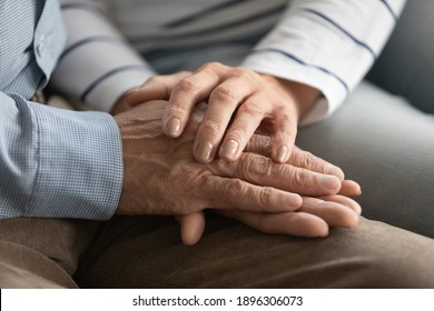 Close up elderly affectionate woman covering wrinkled hands of mature husband, showing love and support at home. Caring middle aged family couple enjoying sincere trustful honest conversation.