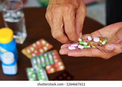 Close up at elderly Asian man holding many pills(tablet and capsule) in hands and pick some medicines for taking supplements antibiotic,antidepressant or painkiller medication Hope for cure.