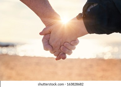 Close up of elderly couple holding hands on the beach at sunset