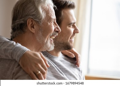 Close up of elderly father and adult grown-up son hug look in distance planning or dreaming together, happy hopeful young millennial man embrace mature dad thinking visualizing good future