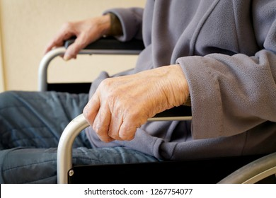 Close up of elderly hands on a wheelchair at home