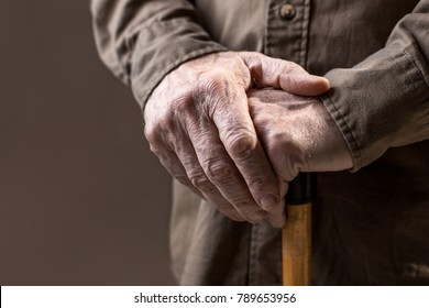 Close up of elderly hands in wrinkles holding walking stick. Isolated on grey background