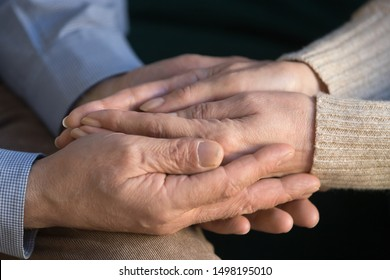 Close up elderly husband holding his wife wrinkled hands, supporting, caring, expressing love and mutual understanding, tenderness, senior man comforting old woman, married couple compassion.