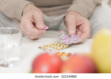 Close up of elderly man holding packaging of tablet pills