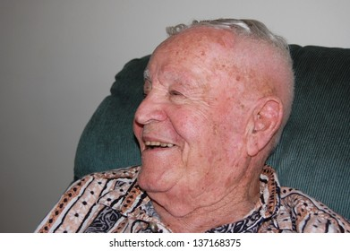 Close up of elderly man smiling to side.
