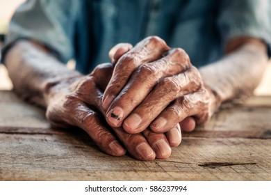 close up of elderly oldman hands on wooden table.vintage effect
