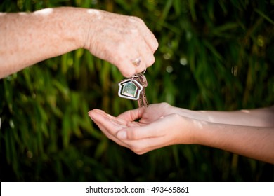 close up of elderly woman hand giving home key to a young person as a legacy symbol