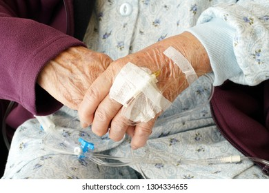 Close up of elderly woman hands with intravenous drip on a wheelchair at hospital