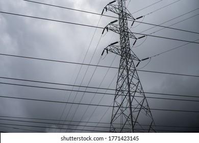 Nahaufnahme eines Elektropolls auf dunklem Himmelshintergrund vor Sturm.