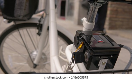 Close up of the electric bicycle battery pack with switch key on the powered ebike and sign Li-ion type with level. E bike shot from behind in the city environment.