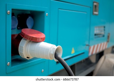 Close up of electric cable with plug on blue mobile generator.