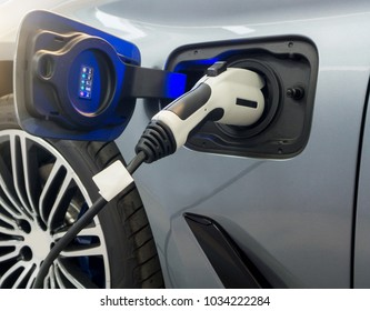 Close up of Electric car socket on process of charging an electric vehicle. Plug the charger Access to vehicle electrification.