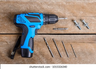 Close up Electric drill, Drill set, Screwdriver set, adapter on wooden table background and copy space. Hammer drill or screwdriver, Electric cordless hand drill on wooden.  maintenance home concept.