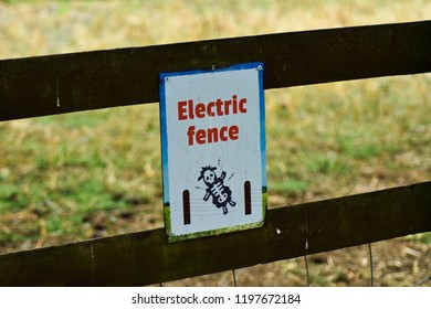 Close up of an electric fence gate caution danger sign with an image of a sheep animal being electrocuted with a warning not to touch the wire.