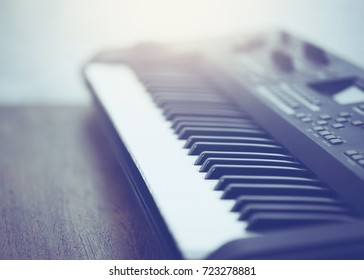 close up of electric Keyboard on wooden table.