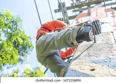 Close up of electrician lineman's foots wearing boots with safety belt climb electric post power pole to install and repair power lines.