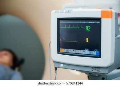 Close up electrocardiograph showing patient heart rate with pacient lying in computed tomography room. Selective focus