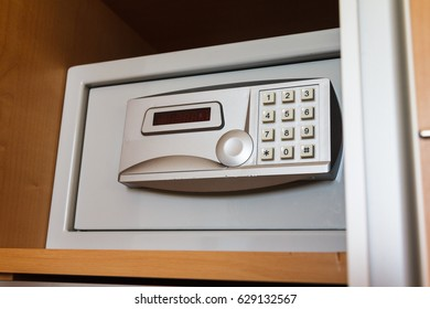 Close up of electronic hotel safe for valuables and money hidden in a secret place of a wooden wardrobe.