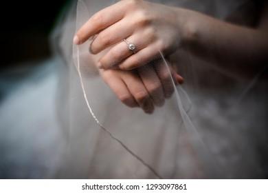 Close up of an elegant diamond ring. Bride hands
