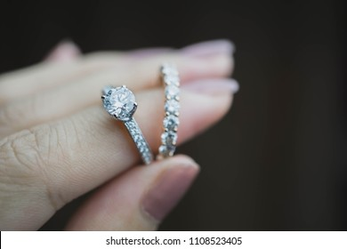 Close up of an elegant diamond ring on woman finger with dark background. soft and selective focus. Love and wedding concept.