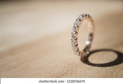 Close up of elegant diamond ring on wooden background. soft and selective focus. Love and wedding concept.