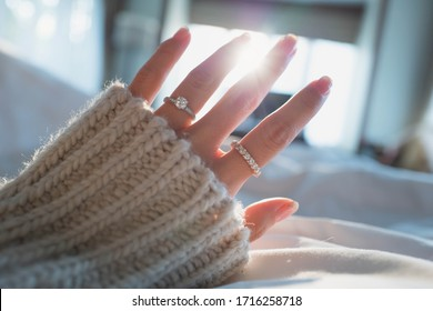 Close up of elegant diamond ring on female finger in morning light. (soft and selective focus)