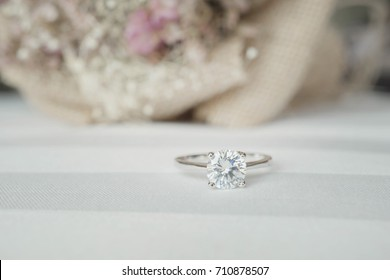 Close up of an elegant diamond ring on the bed with white and pink dried flower bouquet background, soft and selective focus.love and wedding concept.