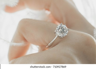 Close up of an elegant diamond ring on the young Asian woman's finger with feather and sunlight background, love and wedding concept. (soft and selective focus)