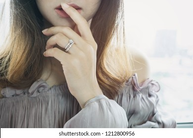 Close up of an elegant engagement diamond ring on beautiful Asian woman's finger with sunlight. love and wedding concept. Split tone Instragram like process.