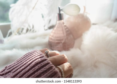 Close up of an elegant engagement diamond ring on woman finger with dark pink sweater winter clothe and blurry perfume and window background. love and wedding concept.soft and selective focus.